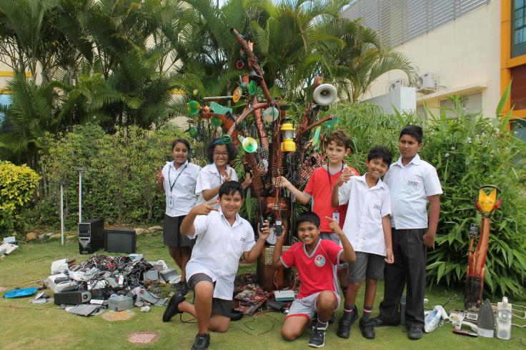 Trio Students pose before tree built of e-waste